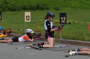 Girl at shooting range on kneeling on skis