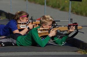 kids laying down shooting a gun